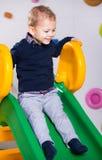 Muchacho que juega en la diapositiva en el patio Fotografía de archivo libre de regalías