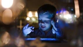 Muchacho que juega en la tableta en café almacen de metraje de vídeo