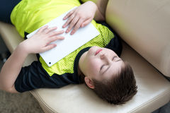 Muchacho que juega en la tableta mientras que miente en el sofá fotos de archivo