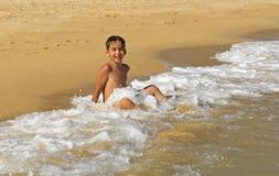 Muchacho que juega en las ondas Foto de archivo libre de regalías
