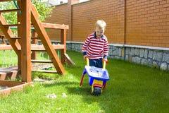 Muchacho que juega en un patio con la arena Imagen de archivo