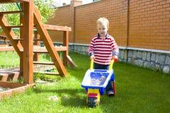 Muchacho que juega en un patio con la arena Fotografía de archivo