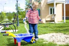 Muchacho que juega en un patio con la arena Imagen de archivo libre de regalías
