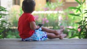 Muchacho que juega en un teléfono móvil almacen de metraje de vídeo
