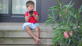 Muchacho que juega en un teléfono móvil almacen de video