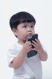 Muchacho que juega en un teléfono móvil en el fondo blanco Imágenes de archivo libres de regalías