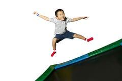 Muchacho que juega en un trampolín Imagen de archivo libre de regalías