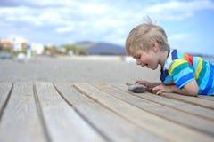 Muchacho que juega en una calzada de madera en la playa Foto de archivo