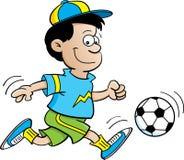 Muchacho que juega a fútbol Fotos de archivo