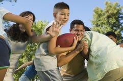 Muchacho (13-15) que juega a fútbol con la familia. fotografía de archivo
