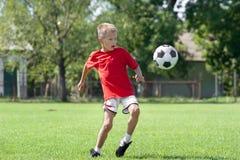Muchacho que juega a fútbol o al balompié Fotos de archivo libres de regalías