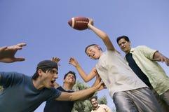 Muchacho (13-15) que juega a fútbol con el grupo de opinión de ángulo de punto bajo de los hombres jovenes. Imagen de archivo libre de regalías