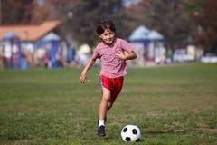Muchacho que juega a fútbol en el parque Fotografía de archivo libre de regalías
