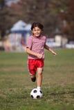 Muchacho que juega a fútbol en el parque Fotos de archivo