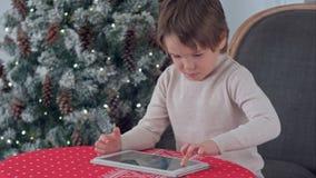 Muchacho que juega a juegos en el suyo tableta que se sienta en la tabla cerca del árbol de navidad Fotografía de archivo