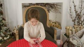 Muchacho que juega a juegos en su teléfono que se sienta en la tabla cerca del árbol de navidad Imagen de archivo libre de regalías