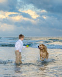 Muchacho que juega la bola con su perro Imagen de archivo