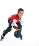 Muchacho que juega la bola en los rodillo-patines Fotografía de archivo