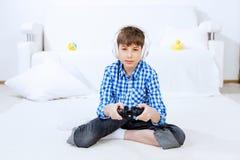 Muchacho que juega la consola del juego Foto de archivo