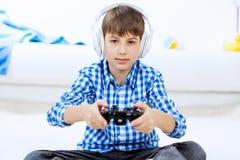 Muchacho que juega la consola del juego Fotografía de archivo libre de regalías