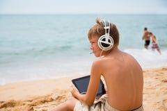 Muchacho que juega la tableta que se sienta por el mar Imágenes de archivo libres de regalías