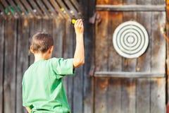 Muchacho que juega los dardos al aire libre Imagenes de archivo