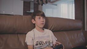 Muchacho que juega a los videojuegos en la consola encendido el sofá en casa almacen de metraje de vídeo
