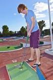 Muchacho que juega a mini golf en el curso Imagenes de archivo