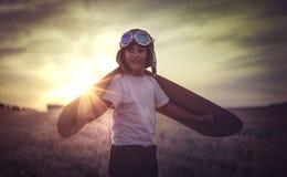 Muchacho que juega para ser un piloto clásico, llevando un sombrero de piel, vidrios Imágenes de archivo libres de regalías