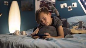 Muchacho que juega smartphone en cama almacen de metraje de vídeo
