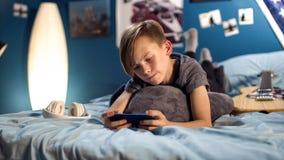 Muchacho que juega smartphone en cama Imagen de archivo libre de regalías