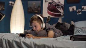 Muchacho que juega smartphone en cama Fotografía de archivo libre de regalías