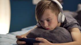 Muchacho que juega smartphone en cama Foto de archivo