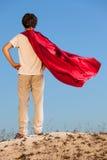 Muchacho que juega a super héroes en el fondo del cielo, fotografía de archivo