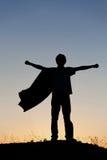 Muchacho que juega a super héroes en el fondo del cielo, fotos de archivo