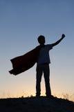 Muchacho que juega a super héroes en el fondo del cielo, silueta de la camiseta imagen de archivo libre de regalías