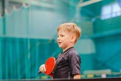 Muchacho que juega a tenis de mesa en el pasillo del tenis fotografía de archivo