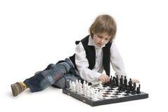 Muchacho que juega a un ajedrez. Imagen de archivo libre de regalías