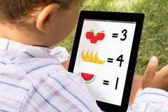 Muchacho que juega y que aprende con la tableta Fotografía de archivo libre de regalías