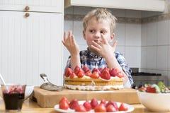 Muchacho que lame el finger con talud de torta de la fresa detrás de una cocina Imagenes de archivo