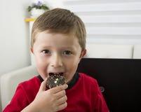 Muchacho que le ofrece una galleta del chocolate Fotografía de archivo libre de regalías