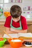 Muchacho que lee el libro del cocinero para hacer la cena Imagen de archivo libre de regalías