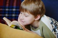 Muchacho que lee en casa Fotografía de archivo
