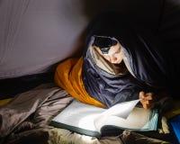 Muchacho que lee un libro con la antorcha en la noche Imagen de archivo