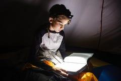 Muchacho que lee un libro con la antorcha en la noche Fotografía de archivo