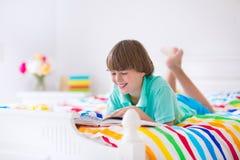 Muchacho que lee un libro en cama Imágenes de archivo libres de regalías