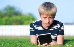 Muchacho que lee un libro en el parque Imagen de archivo