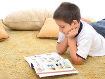 Muchacho que lee un libro en el suelo Foto de archivo libre de regalías