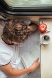 Muchacho que lee un libro en el tren Fotos de archivo