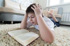 Muchacho que lee un libro mientras que miente en la alfombra en el cuarto Foto de archivo